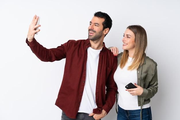 Paar in valentine day over geïsoleerde muur die een selfie met mobiel maken