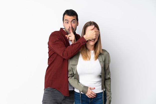 Paar in valentine day over geïsoleerde muur die haar ogen behandelt om haar te verrassen