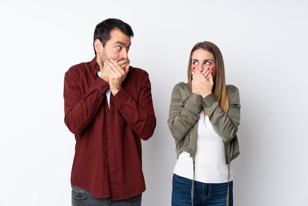 Paar in valentine day over geïsoleerde muur die mond behandelen met handen