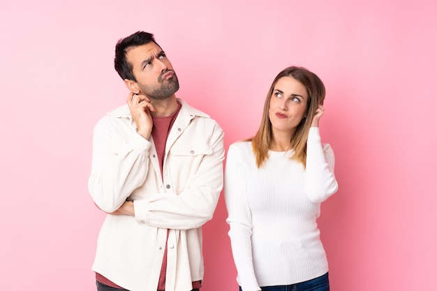 Paar in valentine day over geïsoleerde roze muur die een idee denken terwijl het krassen van hoofd