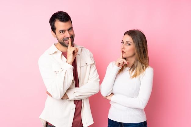 Paar in valentine day over geïsoleerde roze muur die een teken van het sluiten van mond en stiltegebaar tonen