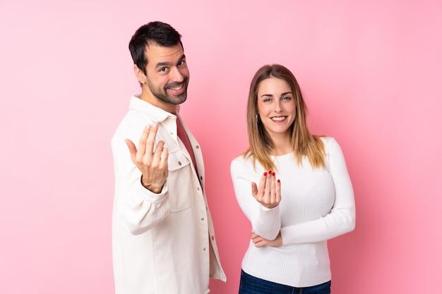 Paar in valentine day over geïsoleerde roze muur die met hand uitnodigt te komen. blij dat je bent gekomen
