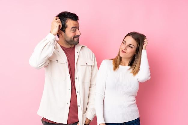 Paar in valentine day over geïsoleerde roze muur die twijfels hebben terwijl het krassen van hoofd