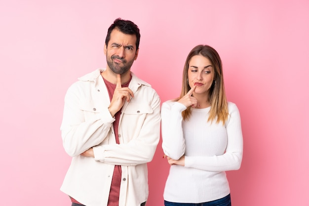 Paar in valentine day over geïsoleerde roze muur die twijfels hebben terwijl omhoog het kijken