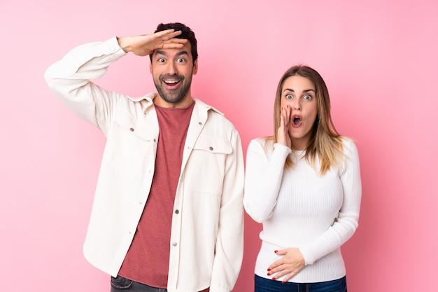 Paar in valentine day over geïsoleerde roze muur verrast en geschokt terwijl het kijken net