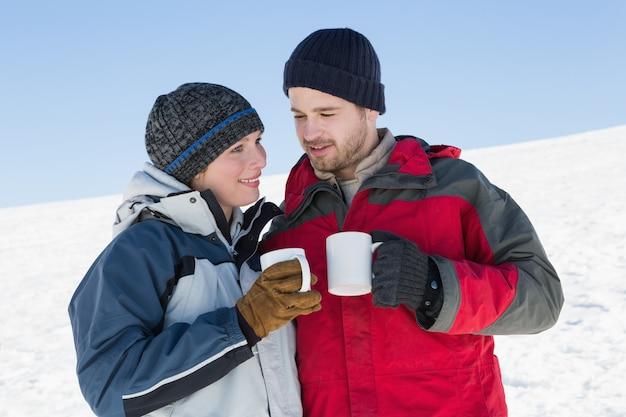 Paar in warme kleding met koffie cups op sneeuw