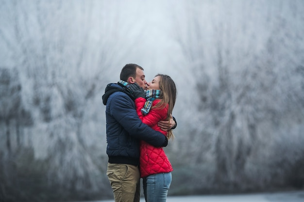 Paar in winter woud in de buurt van meer
