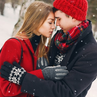 Paar in winterkleren knuffelen op een besneeuwde dag