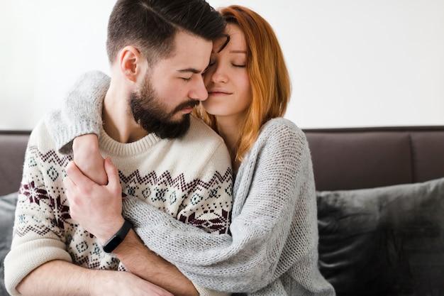 Paar in woonkamer knuffelen close-up