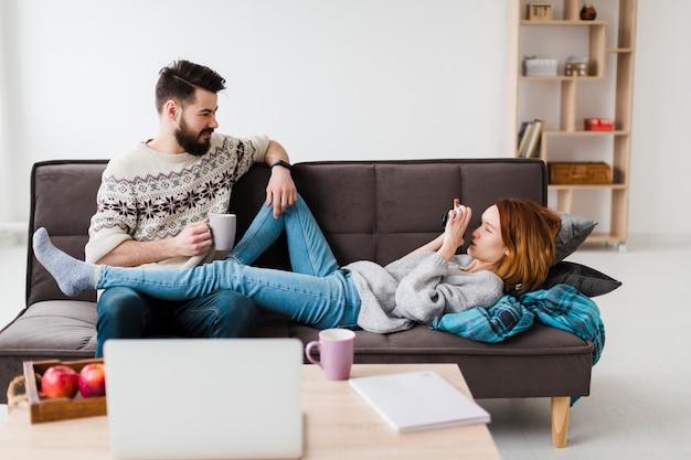 Paar in woonkamer koffie drinken