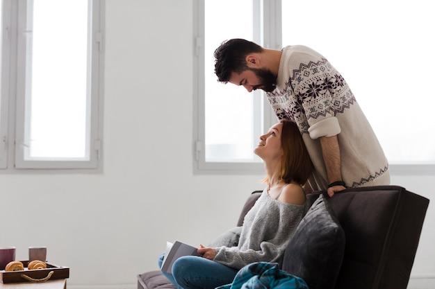 Paar in woonkamer zijwaarts