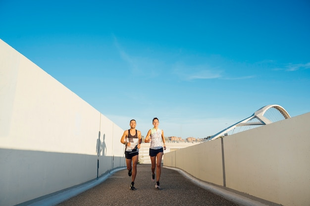Paar joggen tussen twee muren in de stad