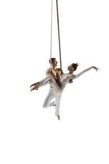 Paar jonge acrobaten, circusatleten op wit wordt geïsoleerd. training perfect uitgebalanceerd tijdens de vlucht