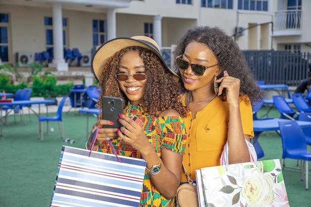 Paar jonge afrikaanse vrouwen die na het winkelen op zoek zijn naar een plek om te eten met hun smartphone