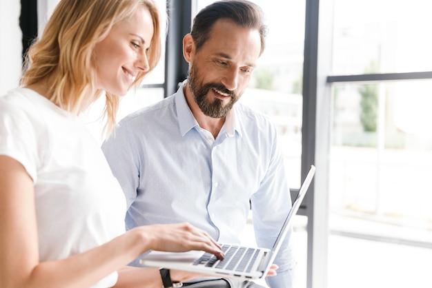 Paar jonge collega's die op laptop computer werken