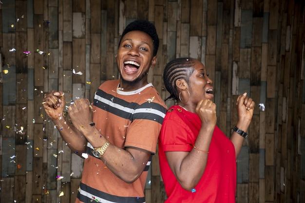 Paar jonge man en vrouw vieren met rondzwevende confetti