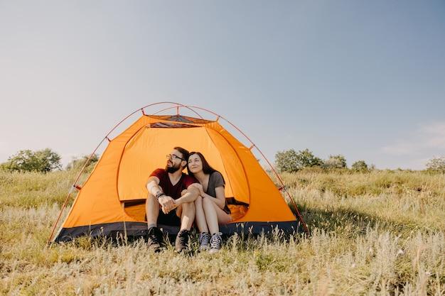 Paar jonge man en vrouw zitten in een oranje tent in de bergen.