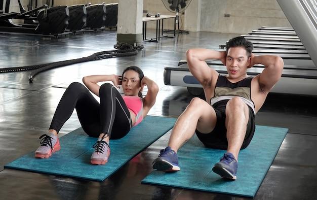 Paar jonge mensen zitten op partner in fitness gym