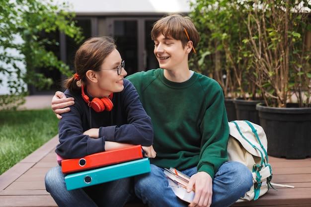Paar jonge studenten zitten met kleurrijke mappen en boeken in handen en vreugdevol