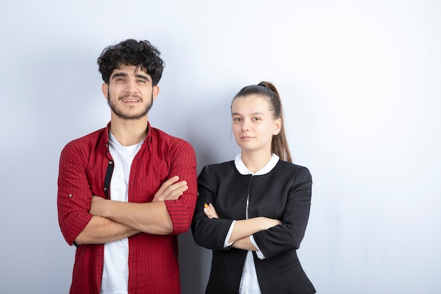 Paar jonge vrienden staande armen gekruist op een witte achtergrond. hoge kwaliteit foto