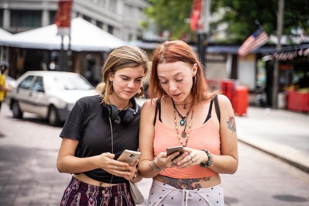 Paar jonge vrouwen kijken naar de mobiele telefoon in de straat