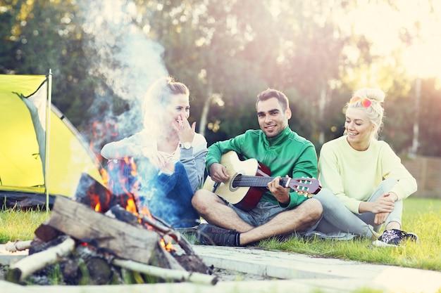 Paar kamperen in het bos en gitaar spelen
