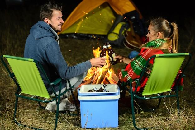 Paar kampvuur tijdens het kamperen bier drinken.