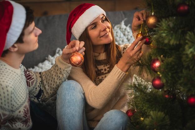 Paar kerstboom versieren