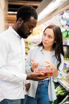 Paar kiezen aardbei in supermarkt