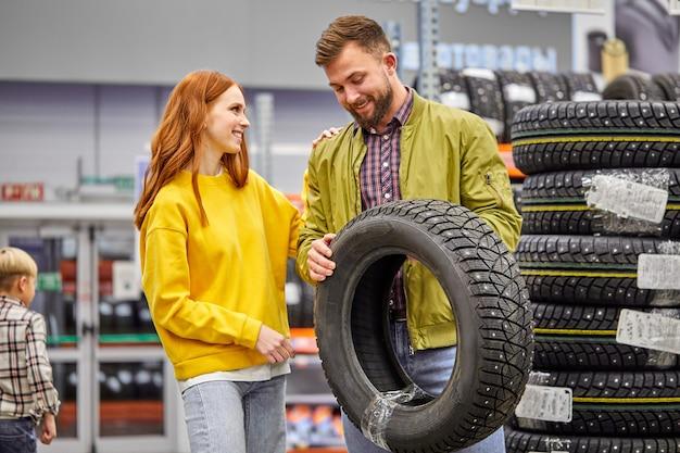 Paar kiezen band voor hun eerste auto in de winkel, bespreken, praten in de winkel, dragen vrijetijdskleding