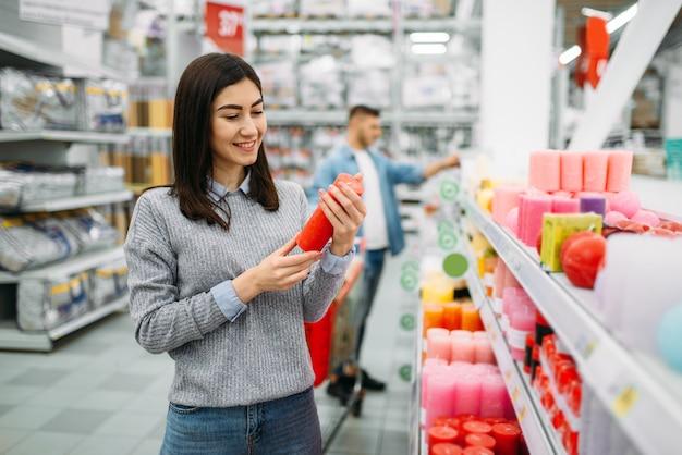 Paar kiezen kaarsen in supermarkt, familie winkelen. klanten in de winkel, kopers in de markt