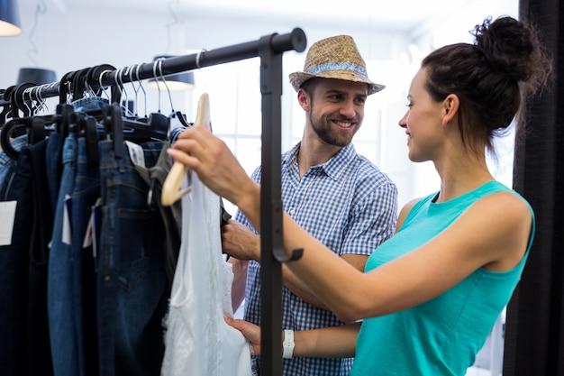 Paar kiezen van kleding uit kleding rack