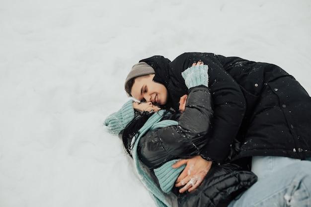 Paar kijken elkaar en glimlachen terwijl liggend op sneeuw.