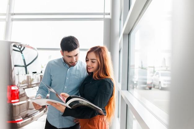 Paar kijken naar autodealer catalogus