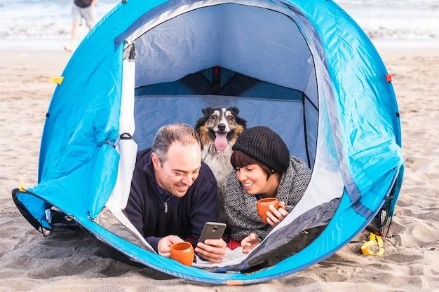 Paar kijken naar de slimme telefoon en veel plezier in een tent in gratis kamperen op het strand hond border collie achter hen kijken naar de camera. vintage kleuren en vakantie familie concept.