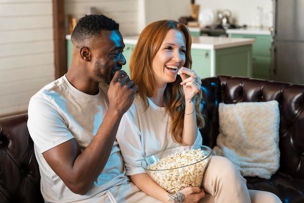 Paar kijken naar een film terwijl ze popcorn eten