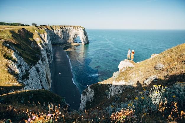 Paar kijken naar etretat kliffen langs de oceaankust in frankrijk