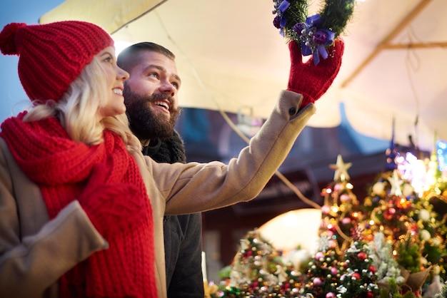 Paar kijken naar kerstkransen