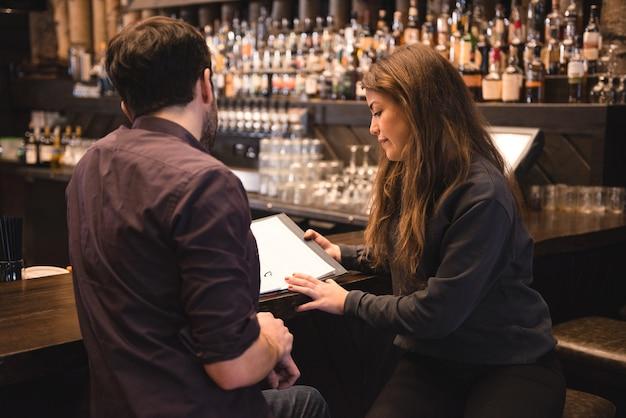 Paar kijken naar menu bij toog