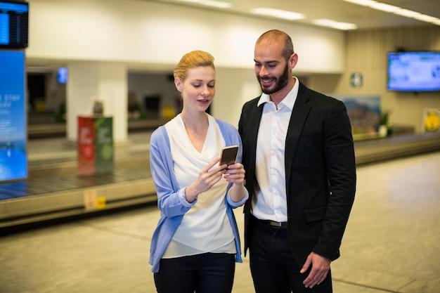 Paar kijken naar mobiele telefoon in wachtruimte