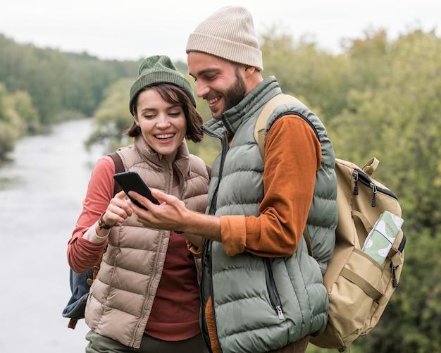 Paar kijken naar telefoon in de natuur