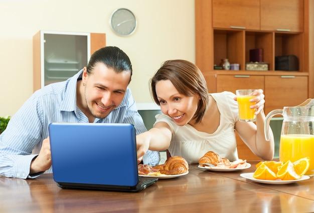 Paar kijkt e-mai tijdens het ontbijt