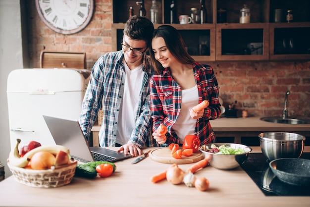 Paar kijkt naar een recept in laptop, salade koken
