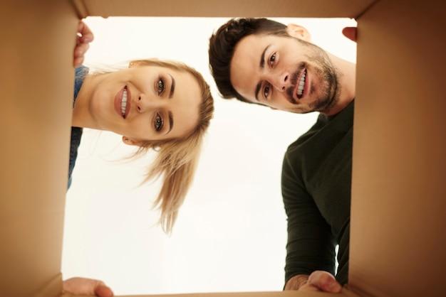 Paar kijkt neer op camera door kartonnen doos