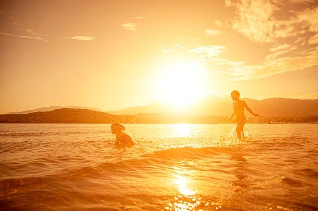 Paar kinderen die in het overzees spelen, schot dat bij zonsondergang wordt genomen