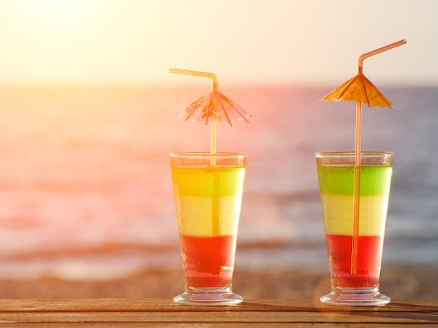 Paar kleurrijke cocktails op het strand en de zee