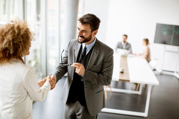 Paar knappe multi-etnische zakenmensen handenschudden op kantoor
