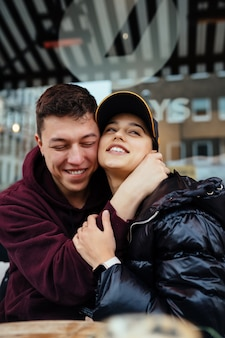 Paar knuffelen aan een tafel op een terras