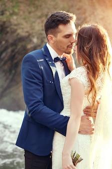 Paar knuffelen bij zonsondergang, geliefden paar zoenen in zonsondergang. huwelijksceremonie buitenshuis. mooie bruid en bruidegom met boeket bloemen. witte trouwjurk voor bruid. liefde bruidspaar knuffel. vervaagd