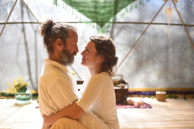 Paar knuffelen en kijken elkaar in tantra yoga